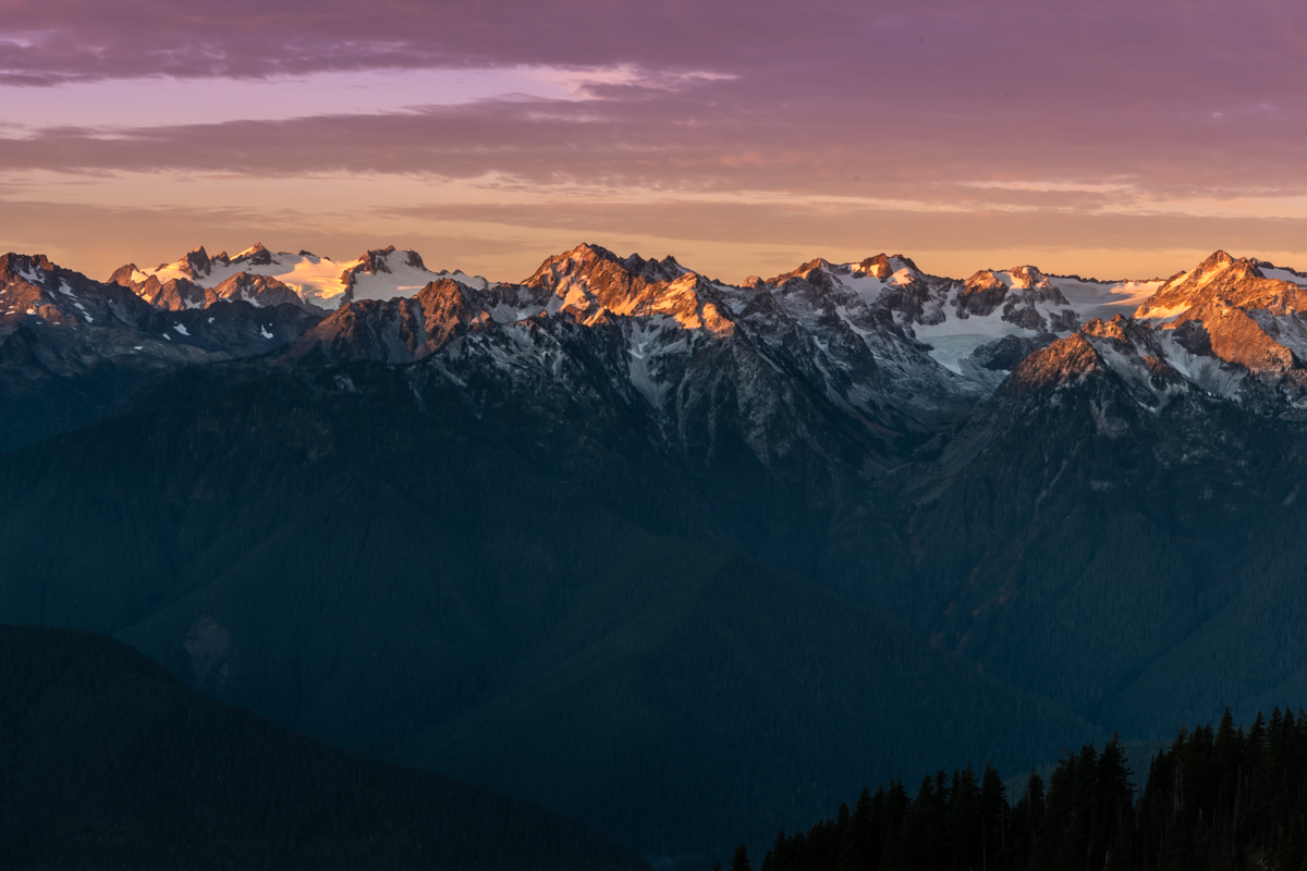 Pink Light from Sunrise Reflects Over Mountain Range