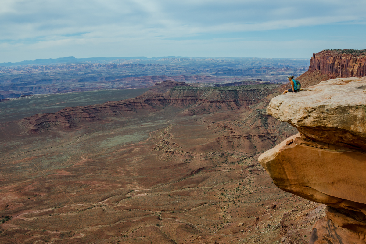 Female Hiker Looks Down Over Grand View in Island in the Sky
