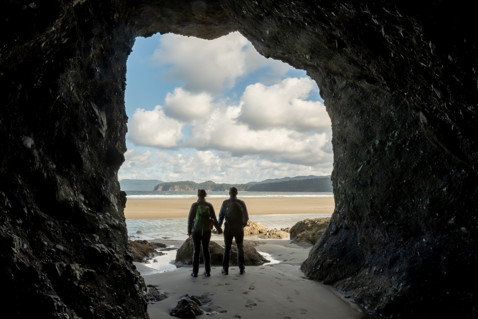 Hiker Couple Hold Hands In Sea Cave