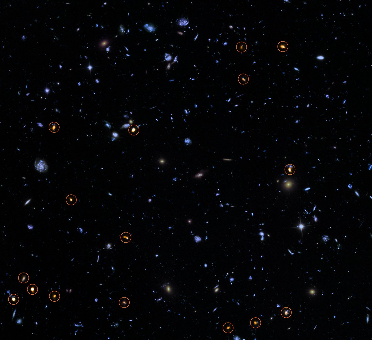 This image combines a background picture taken by the NASA/ESA Hubble Space Telescope (blue/green) with a new very deep ALMA view of this field (orange, marked with circles). Credit: ALMA (ESO/NAOJ/NRAO)/NASA/ESA/J. Dunlop et al. and S. Beckwith (STScI) and the HUDF Team.
