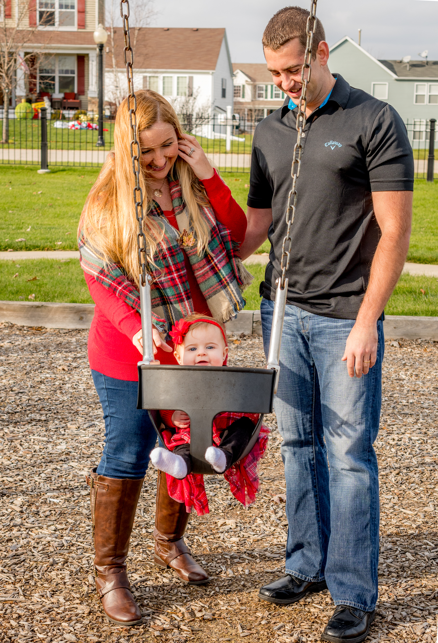 A mother and father push their baby daughter on the swings for a family session in Antioch Illinois