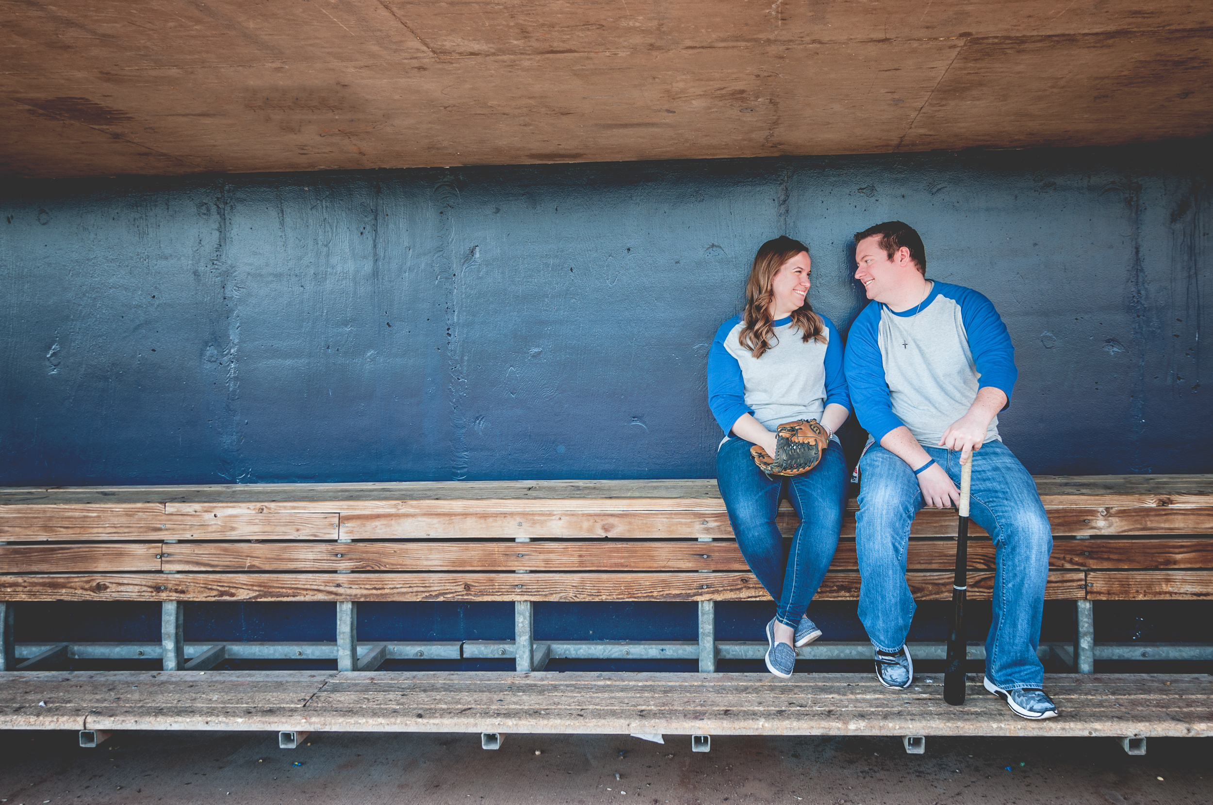 a woman and man in baseball shirts sit in the dugout for their engagement session at Modern Woodmen Park