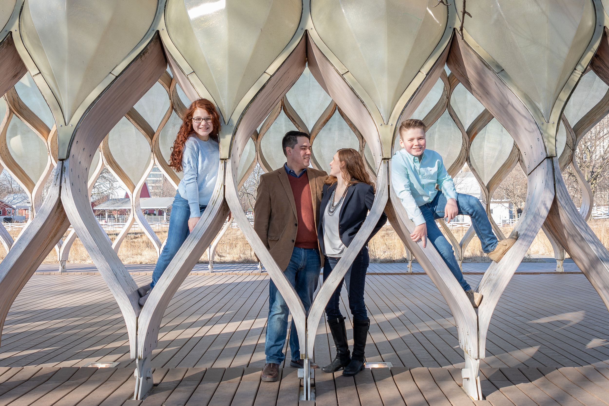 a man, woman, 12 year old girl, and 10 year old boy pose for family pictures at The Honeycomb pavilion on Lincoln Park's Nature Boardwalk