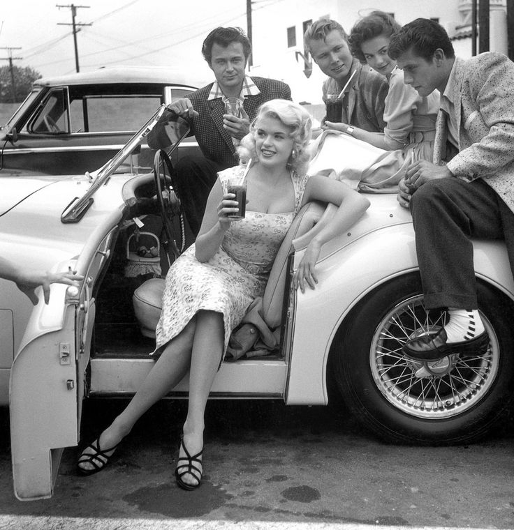 1950s Hollywood starlet Jayne Mansfield posing with admirers in a Jaguar XK120