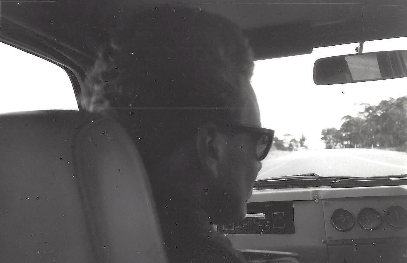 The author in the passenger seat - cheap sunglasses and no windscreen at 110kph on the Princes Hwy