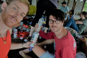 Matt and Daniel stuff plastic bottles together in Bali to make plastic bricks, a great effort to conserve plastic - but hard work!