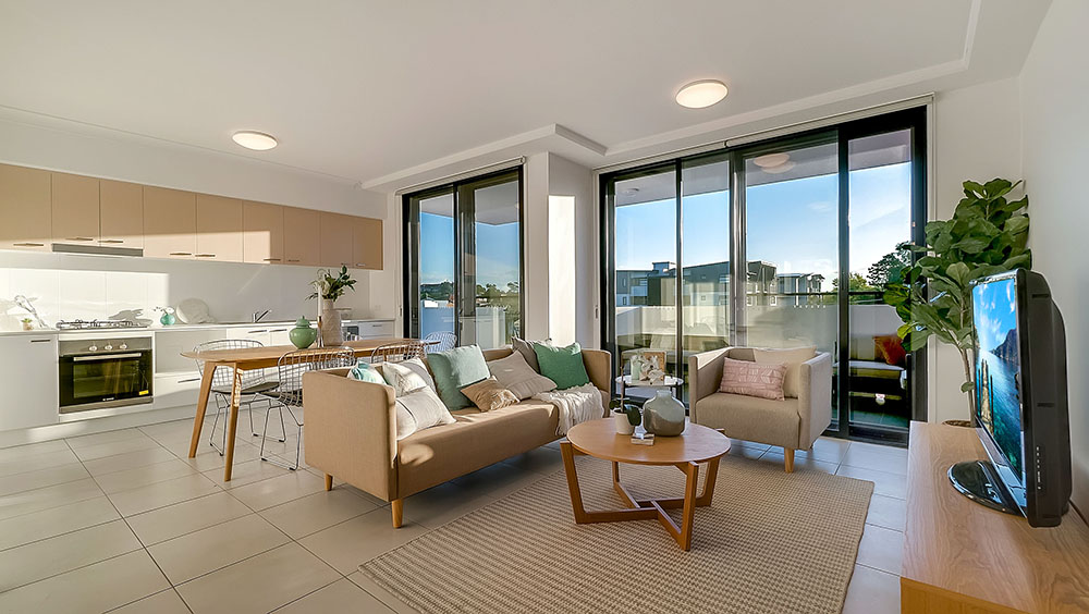 Real estate internal photography of spacious living area for marketing an apartment in Brisbane with glass doors onto a patio.