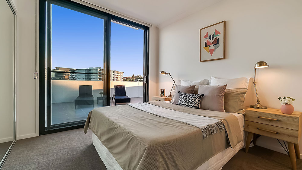 Internal real estate photography of Brisbane apartment bedroom with glass doors onto a private patio — excellent professional marketing.