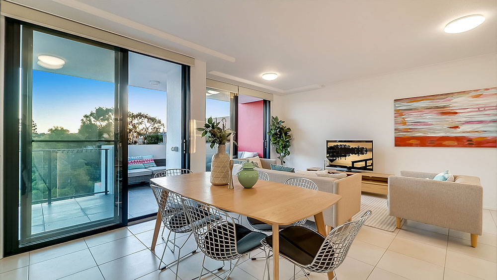 Real estate photography of Brisbane apartment living area with glass doors onto balcony.
