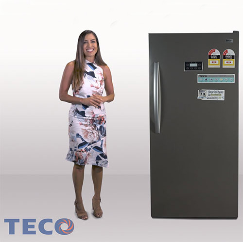 Woman in the TECO commercial standing next to a stainless steel TECO fridge.