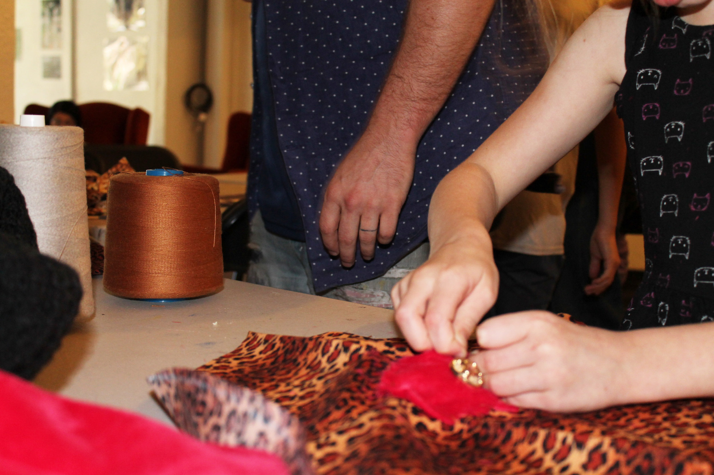 Embellishing a leopard print heart shaped pillow with gold buttons and pink felt before adding stuffing and finishing.