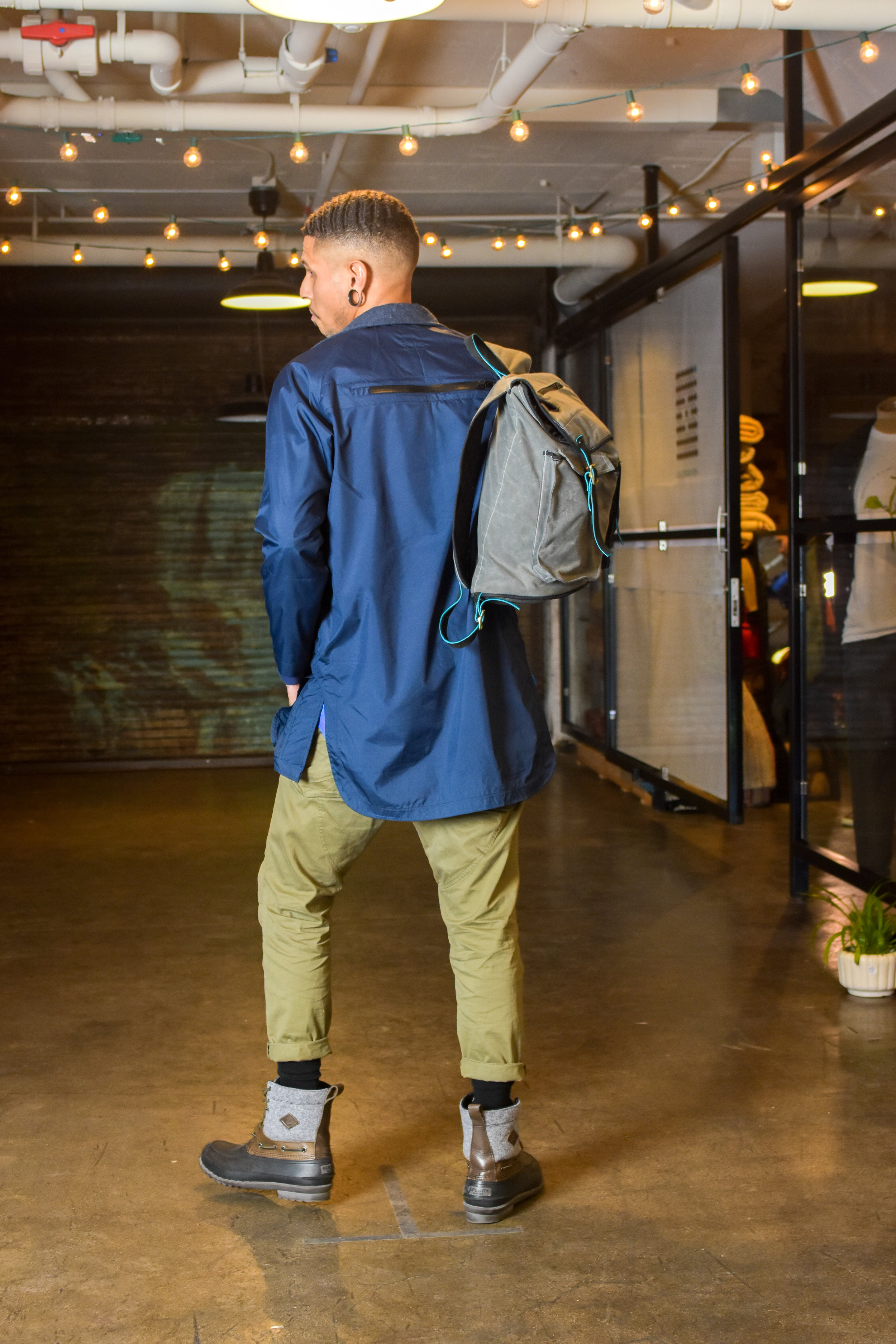 Blue lightweight nylon Mac coat with wool details, cotton trousers, backpack inspired by vintage fishing baskets.