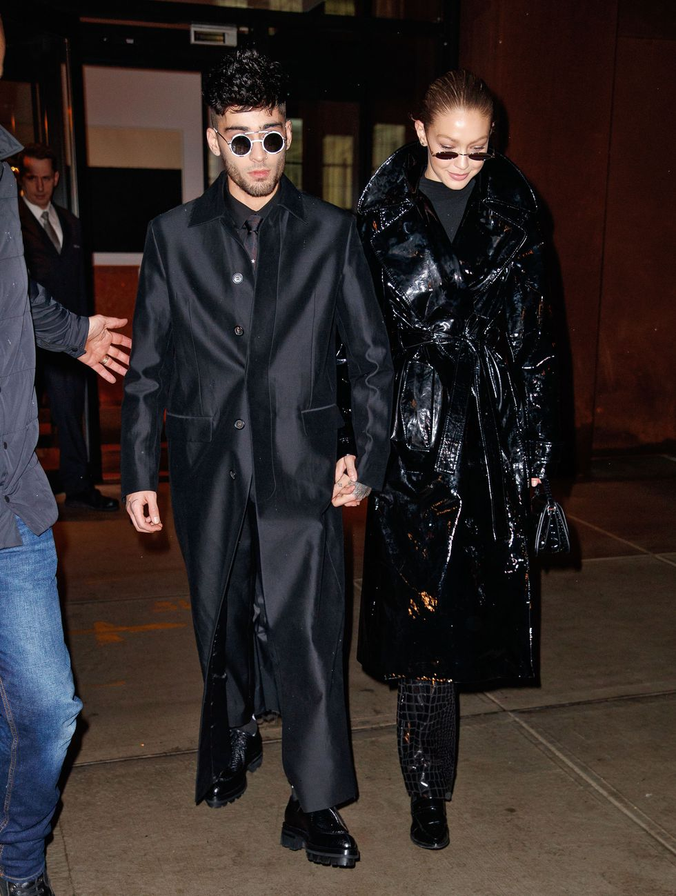 Gigi Hadid and Zayn rock patent black trench coats complete with matrix-style sunglasses - R.I.P. Gee Zee. Photo by Getty Images
