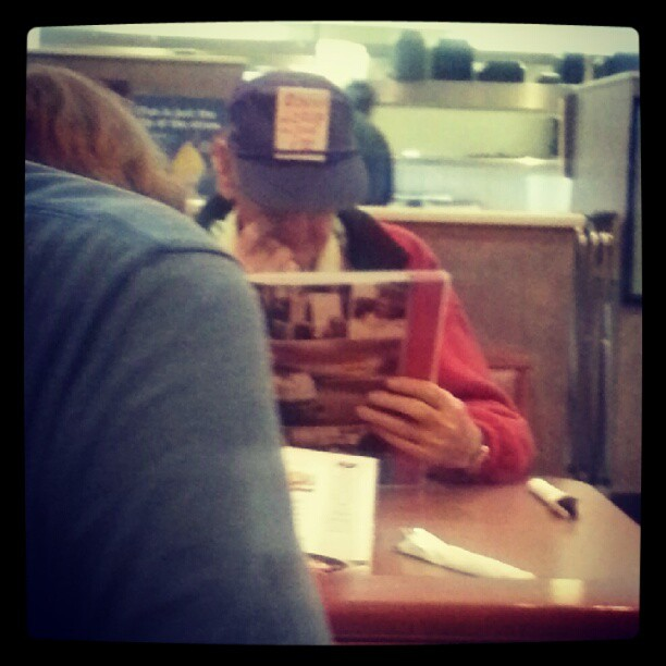 """Sometimes you have to go to Denny's on a roundtrip. And sometimes you see this guy who has an index card in his old man hat with a hand written """"Obama + crap =she It!"""""""