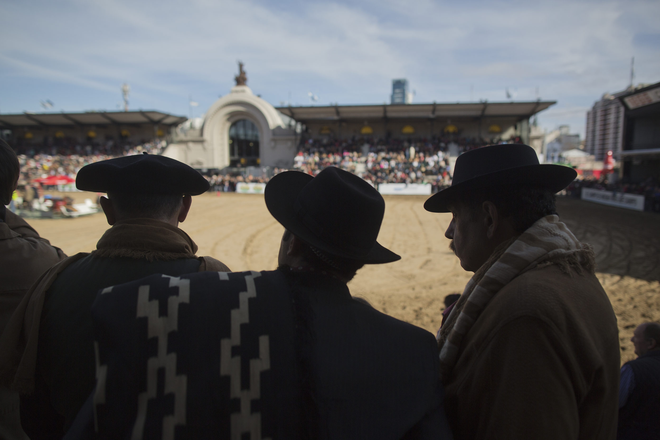 Gauchos watch horse competitions at the Rural Exposition in Buenos Aires.