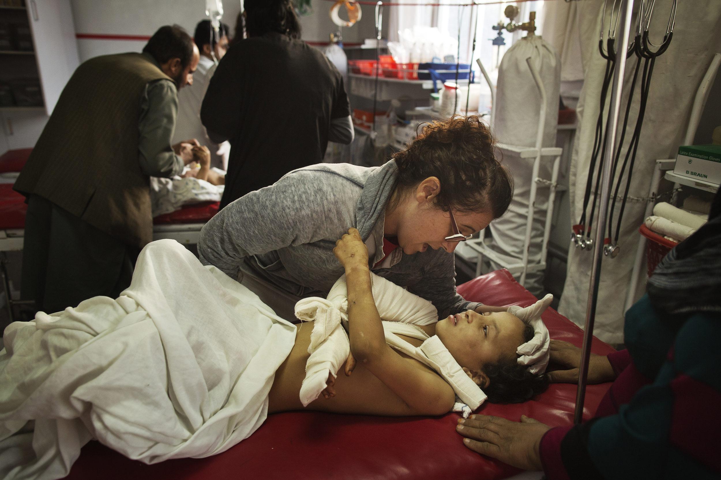 Nurse Georgia Novello comforts Madina, 8, injured in the US airstrike on the MSF hospital in Kunduz and evacuated to Kabul.