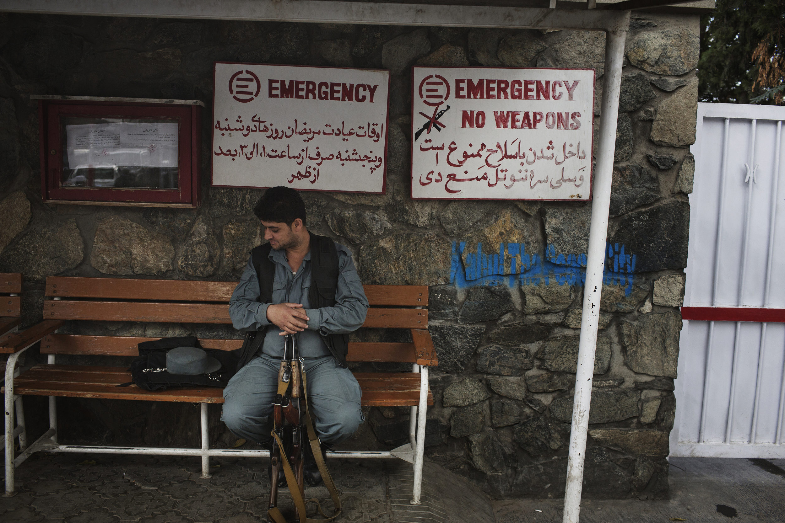 An Afghan policeman waits with his companions weapons, prohibited inside the hospital.