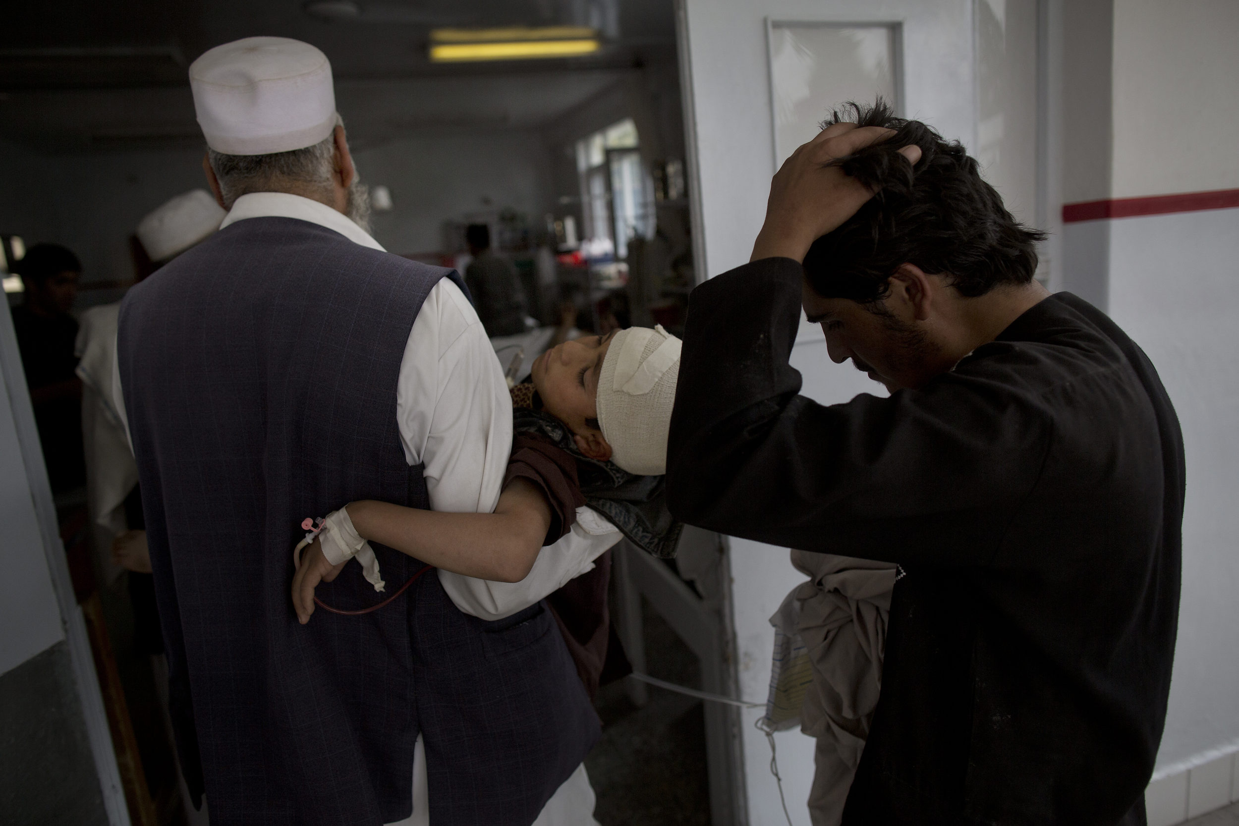 A family brings in Abdul Rashid, 10, who received shrapnel to the head in a blast
