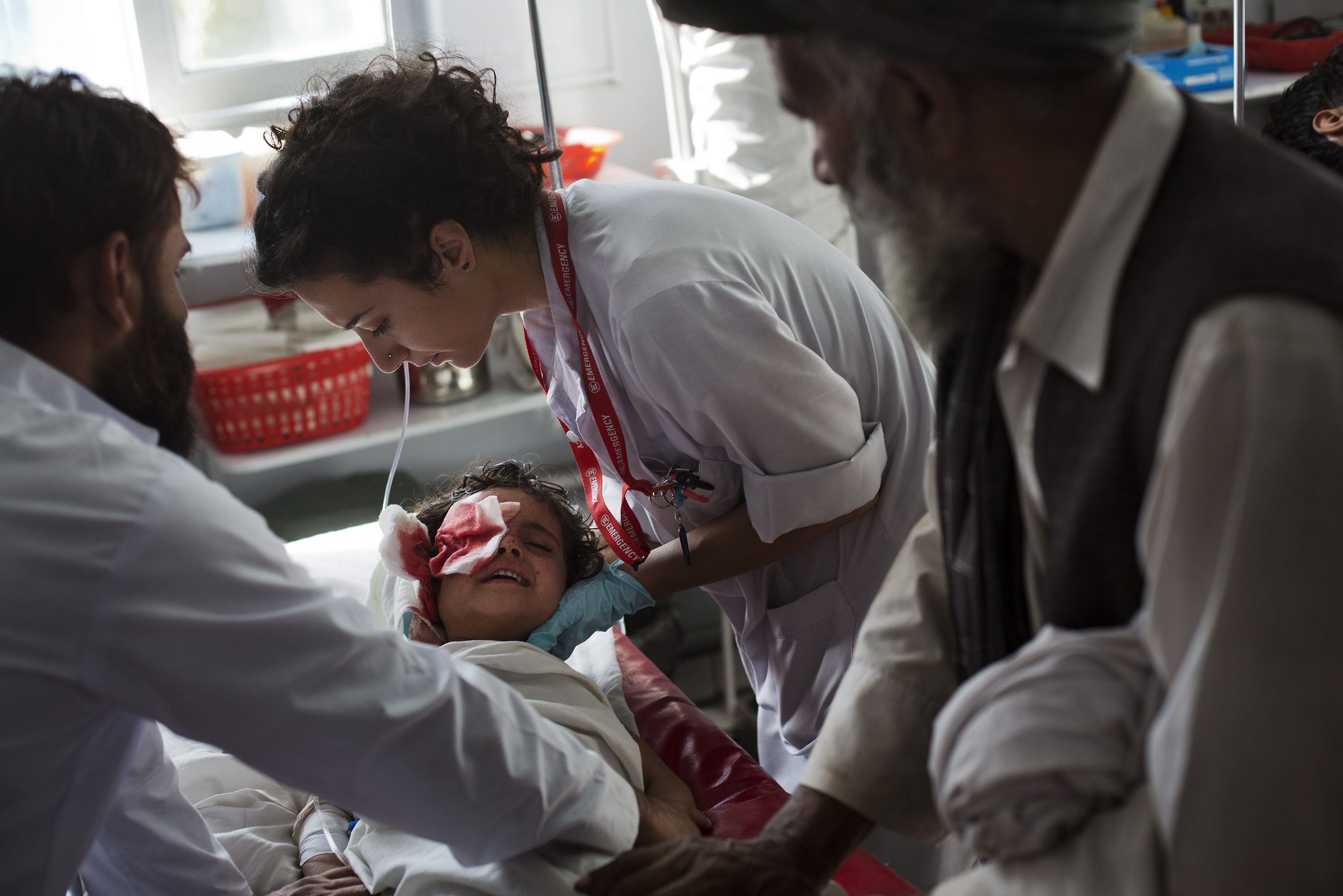 Head nurse Tijana Maričīć cradles the head of Nadia, 6, from Lalandar, a village outside of Kabul, who lost her eye and much of the side of her face playing with an unexploded munition