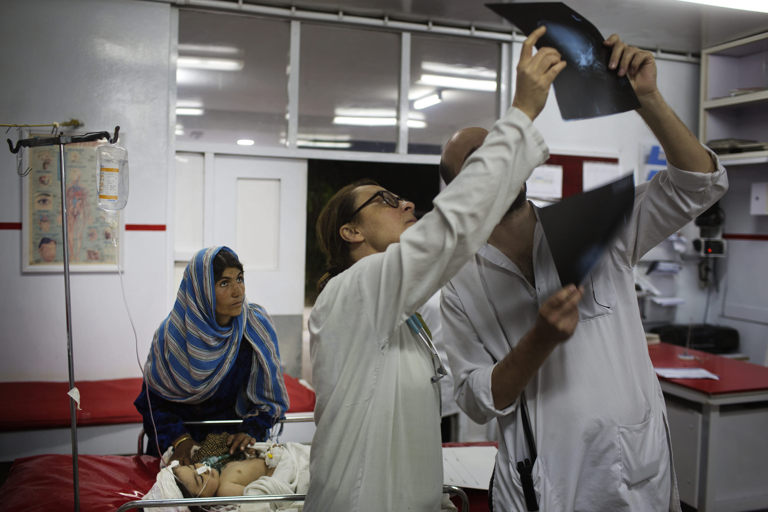 Emergency doctors look over the X-rays of Nasirullah, 1, who suffered a shrapnel injury to her head in Ghazni.