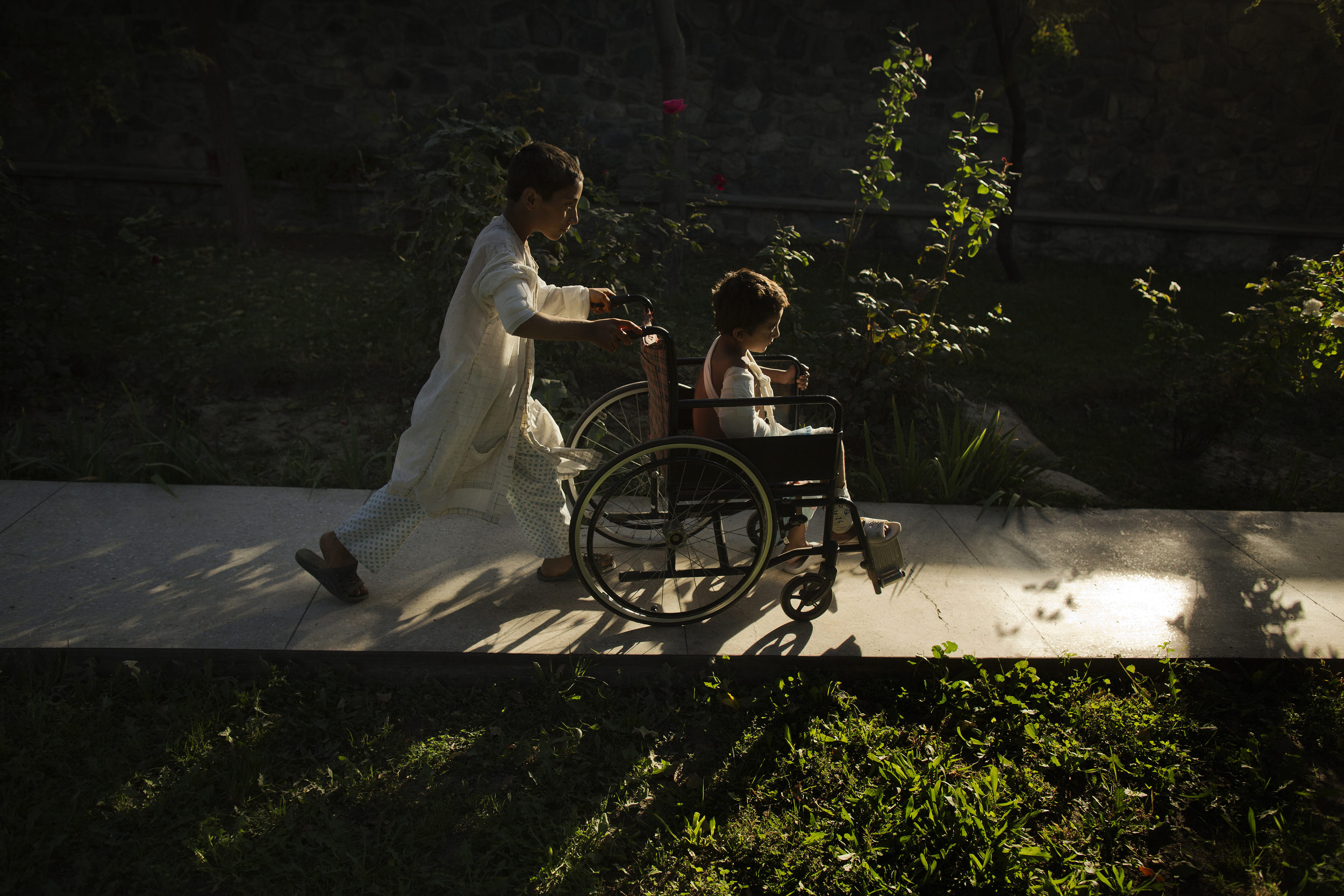 Ajmal 11, pushes Sangeer, 7, along a path in the hospital.