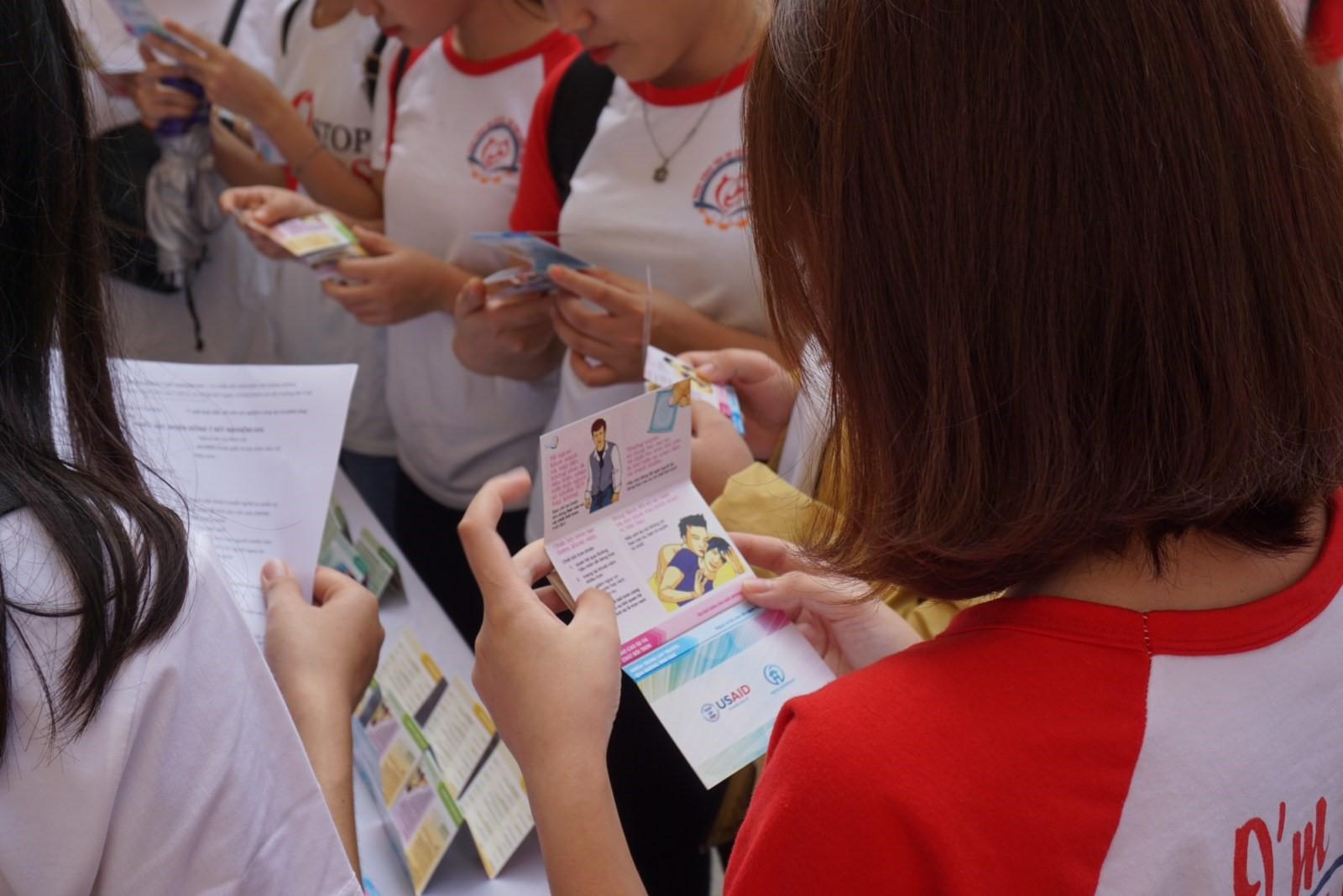 Các sinh viên tham gia công tác xã hội của Trường Đại học Công đoàn đang xem lại tài liệu truyền thông tại gian hàng xét nghiệm HIV do USAID tài trợ