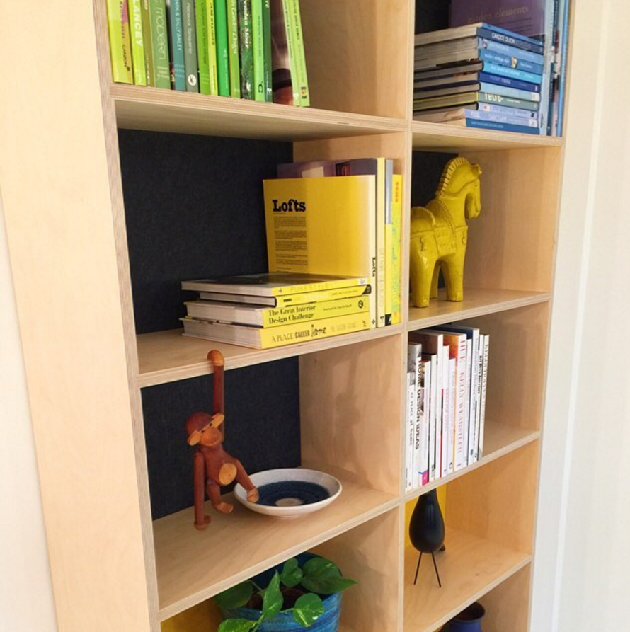 A modular plywood shelving unit with grey acoustic backing.