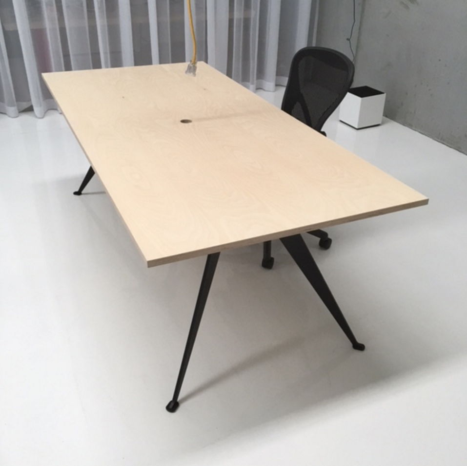 Stealth table with premium birch plywood top and powder-coat legs, central cable access.