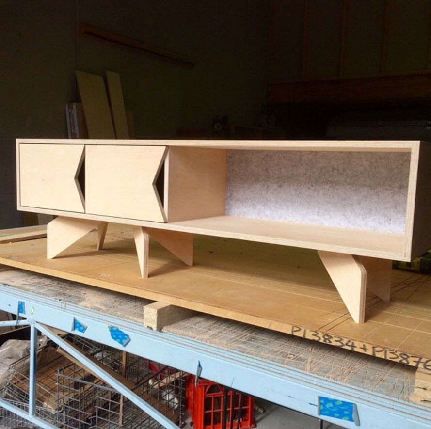 Standard plywood entertainment unit with envelope pull detail, grey acoustic backing and plywood rocket legs