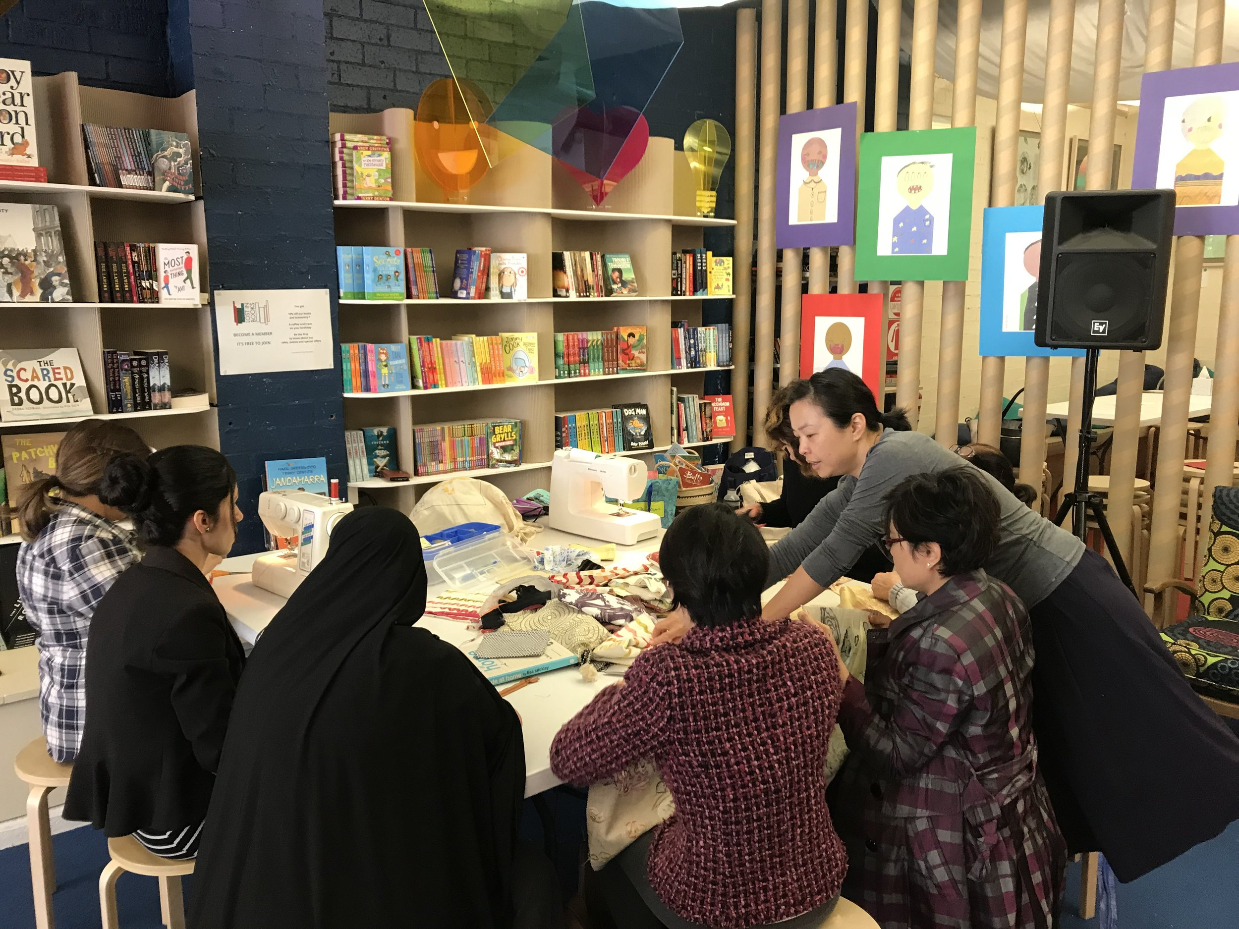 Nga Le (standing) facilitating the weekly textiles group at Lost In Books