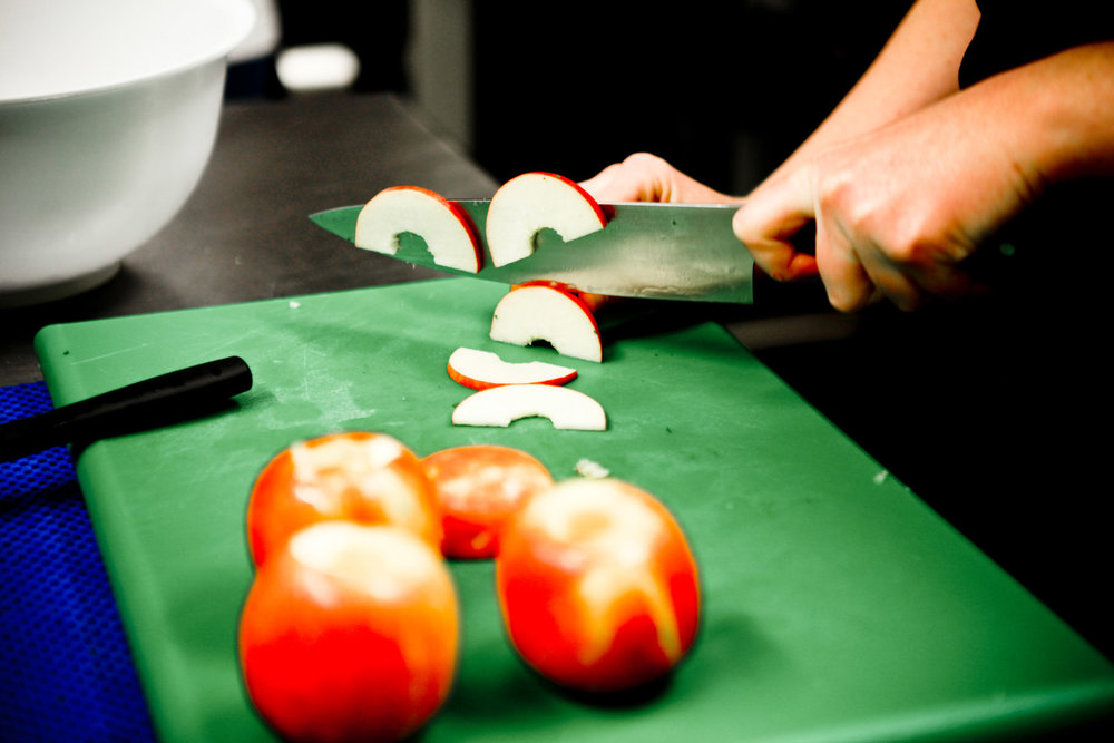 Cored apples being chopped on a chopping board