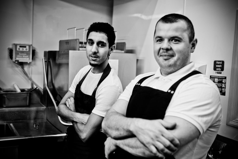 A black and white photograph of chefs posing in the kitchen