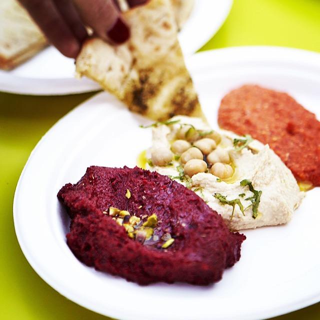 A dish of hummus, tapenade and tzatziki
