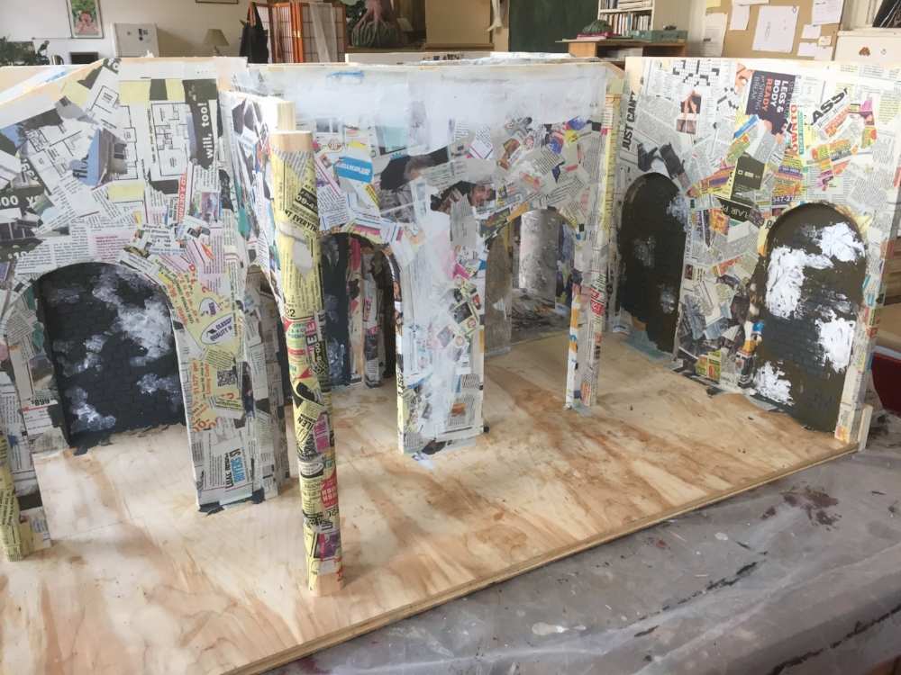The constructed set, with high arches and niches for the artworks, gets covered in paper-maché and with bricks made of cardboard.