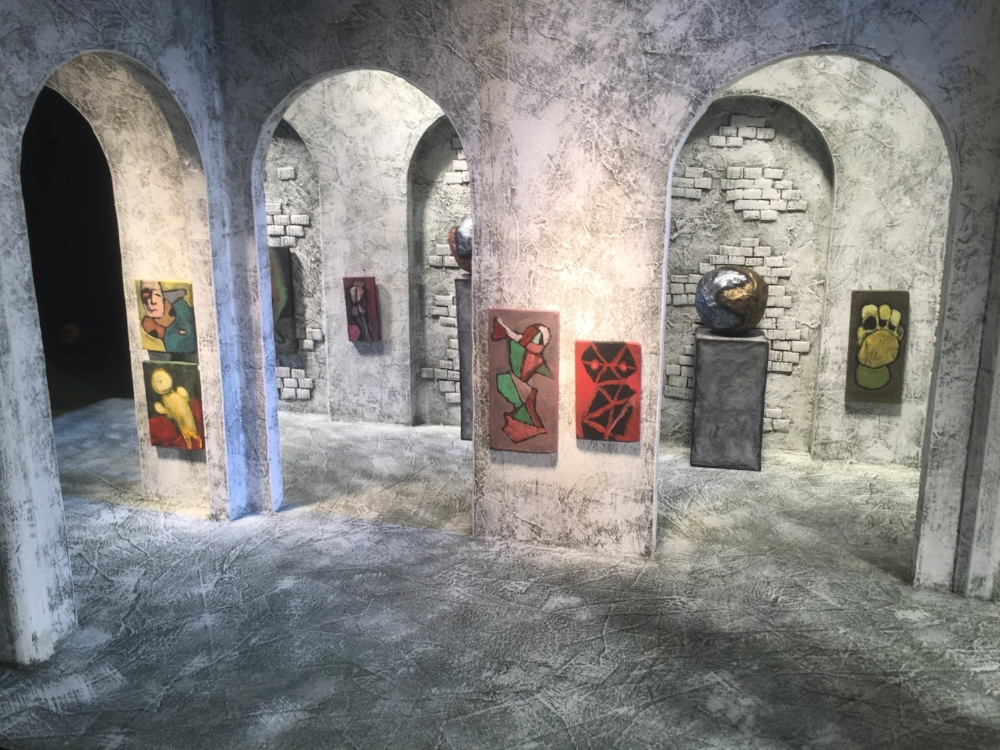 The left side of the gallery, with artworks placed on the walls and sculptures placed in the niches.