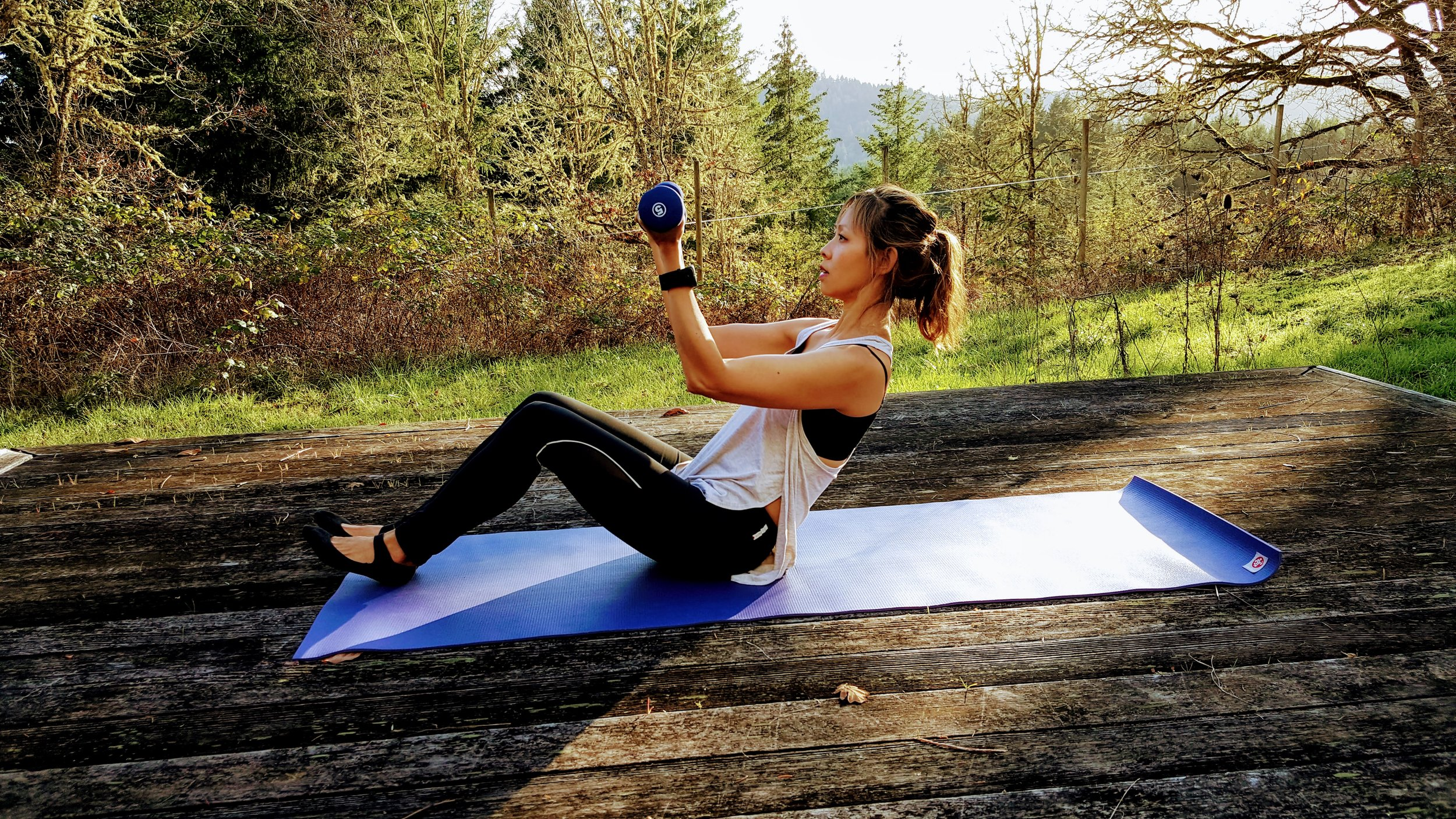 9.    Come to a sitting position, bend your knees and dig the back of your heels into your mat. Inhale and as you exhale out of your mouth, draw your abdominals in as you curl back. Using weights (here I am using 5 pounds) or soup cans, bend and extend your arms for 8-10.