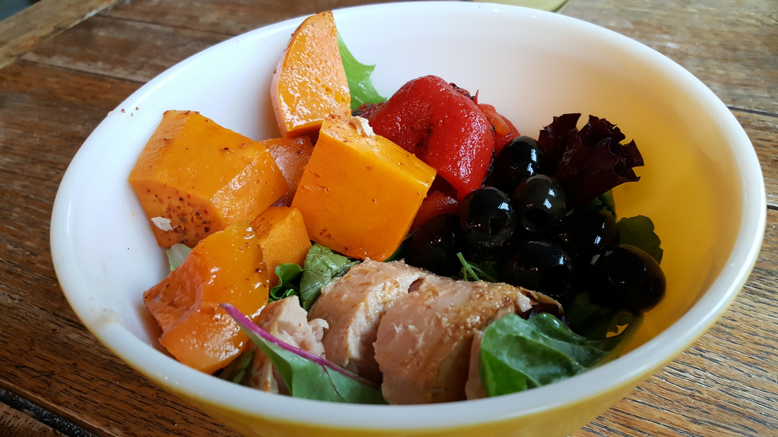 Salad bowl of butternut squash, greens, roasted red peppers, tuna and olives