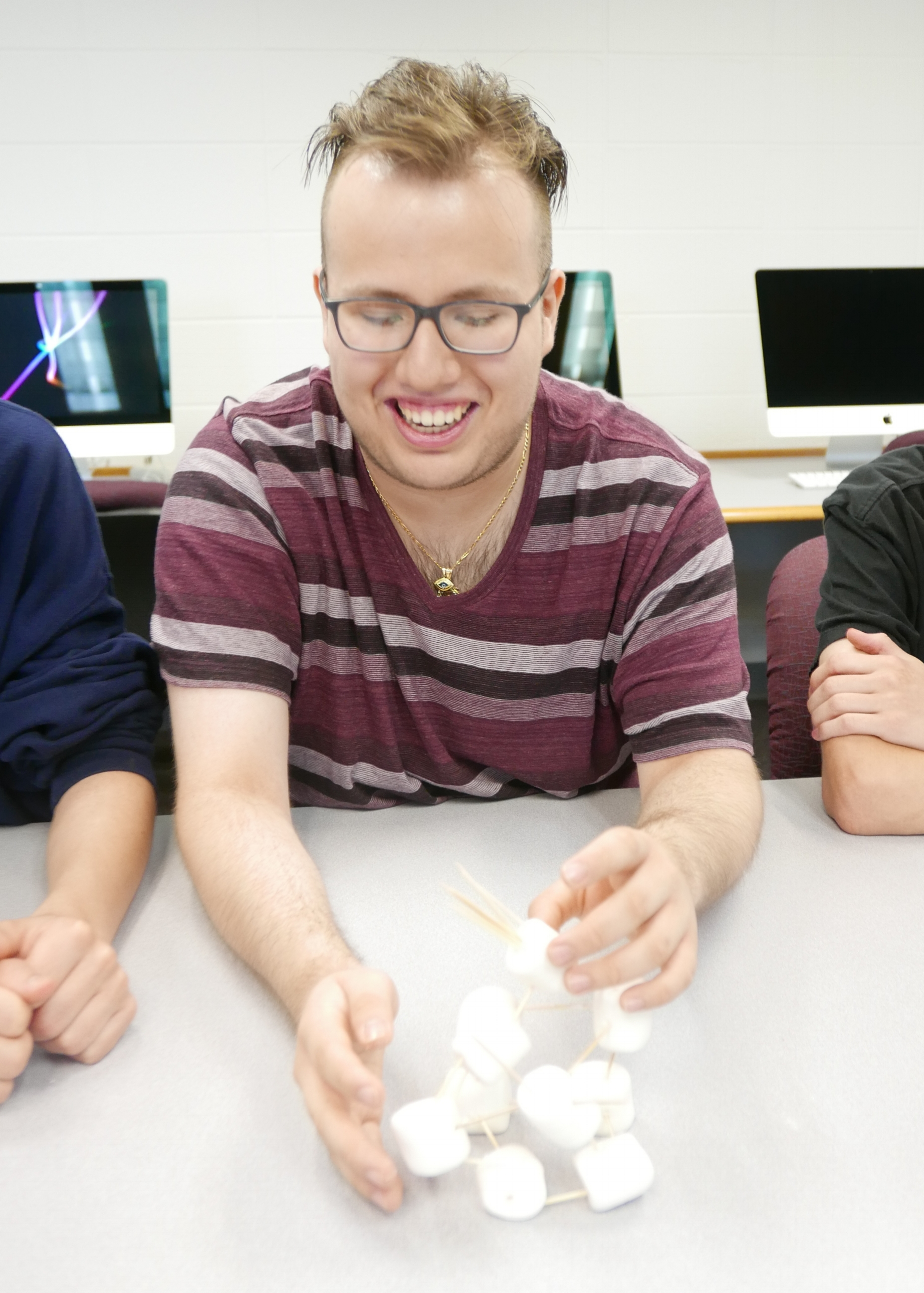 During a team building challenge, Uriah Munoz holds together a marshmallow tower.