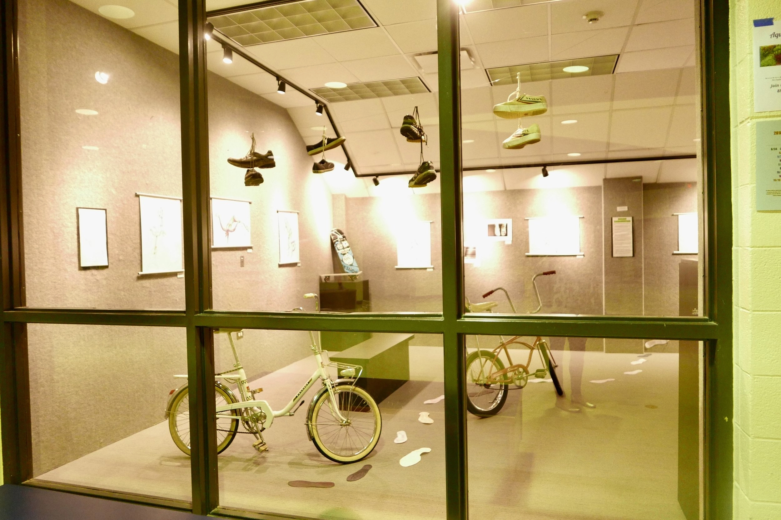 students collected alternative transportation methods such as bicycles, skateboards and shoes from staff to include in the gallery's first environmental show.