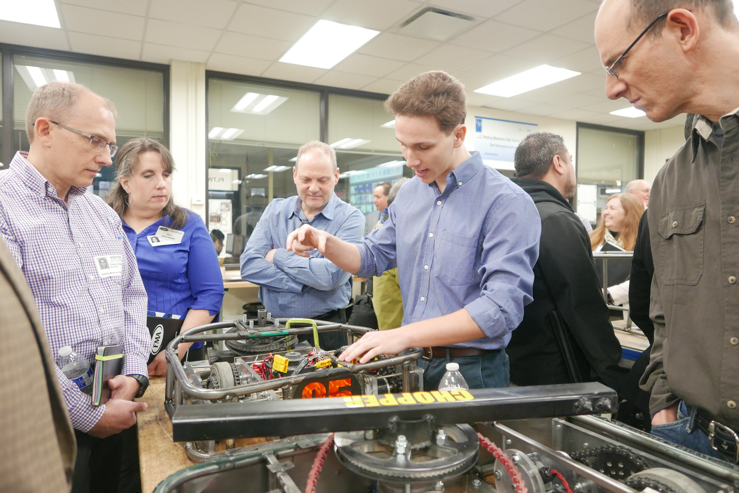 Rolling Meadows junior Boris Jevtic shows area manufacturers the kinds of real-world projects students work on in District 214.
