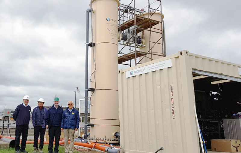 From left to right:    Joe Goergen, Dr. David Rhu, Dr. Glen Daigger, Dr. Joh Kang standing in front of the two pilot-scale Proteus Reactors in Flint, Michigan.