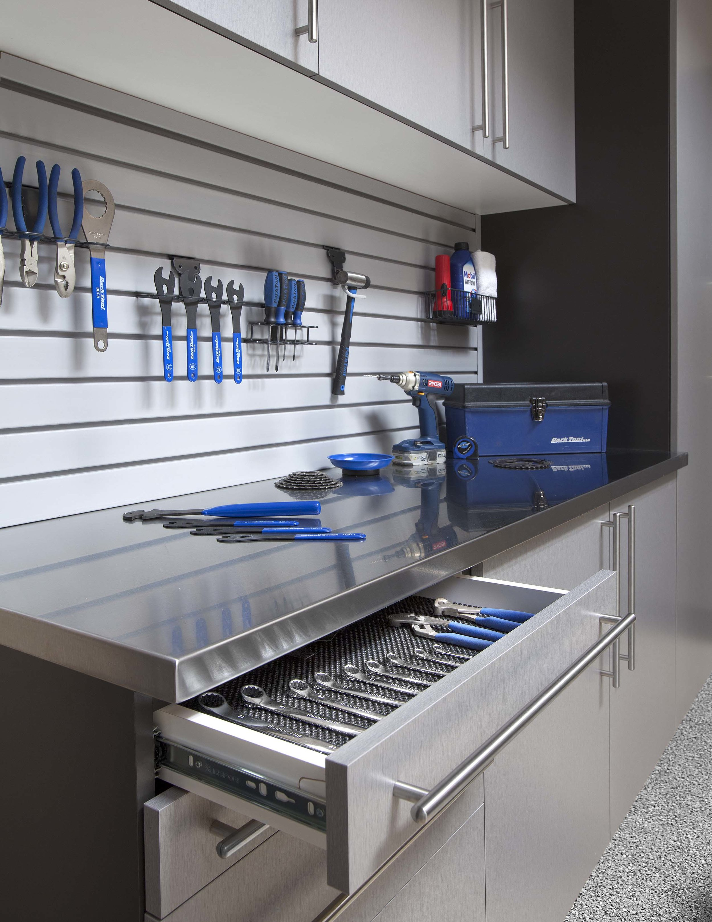 Slatwall tool storage completes a custom tool cabinet.  Call Closets of Tulsa  today for a FREE consultation and 3-D garage design:  918.609.0214
