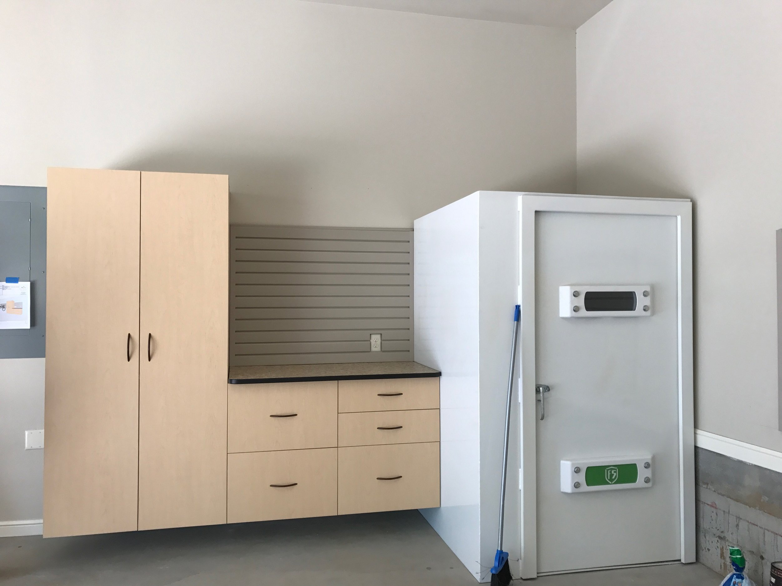 Great garage cabinets maximize storage with limited space. Pictured: Maple garage cabinets and slatwall mounted between a storm shelter and a breaker box.  Call Closets of Tulsa  today for a FREE consultation and 3-D garage design:  918.609.0214