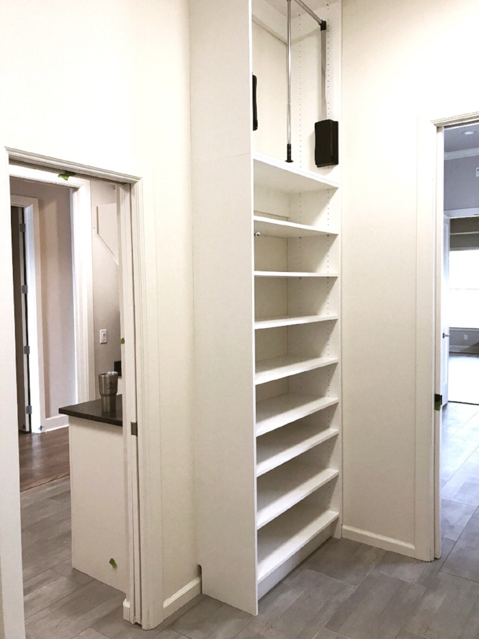 A space saving shoe rack and pull down closet rod make the most of a small (tall) corner in this custom closet by Closets of Tulsa.  Call Closets of Tulsa  today for your FREE consultation and 3-D closet and garage design:  918.609.0214