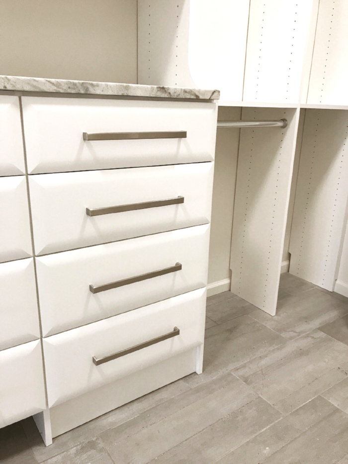 Brushed stainless drawer pulls and pillow top drawer faces add touches of luxury to this custom master closet by Closets of Tulsa.  Call Closets of Tulsa  today for your FREE consultation and 3-D closet and garage design:  918.609.0214
