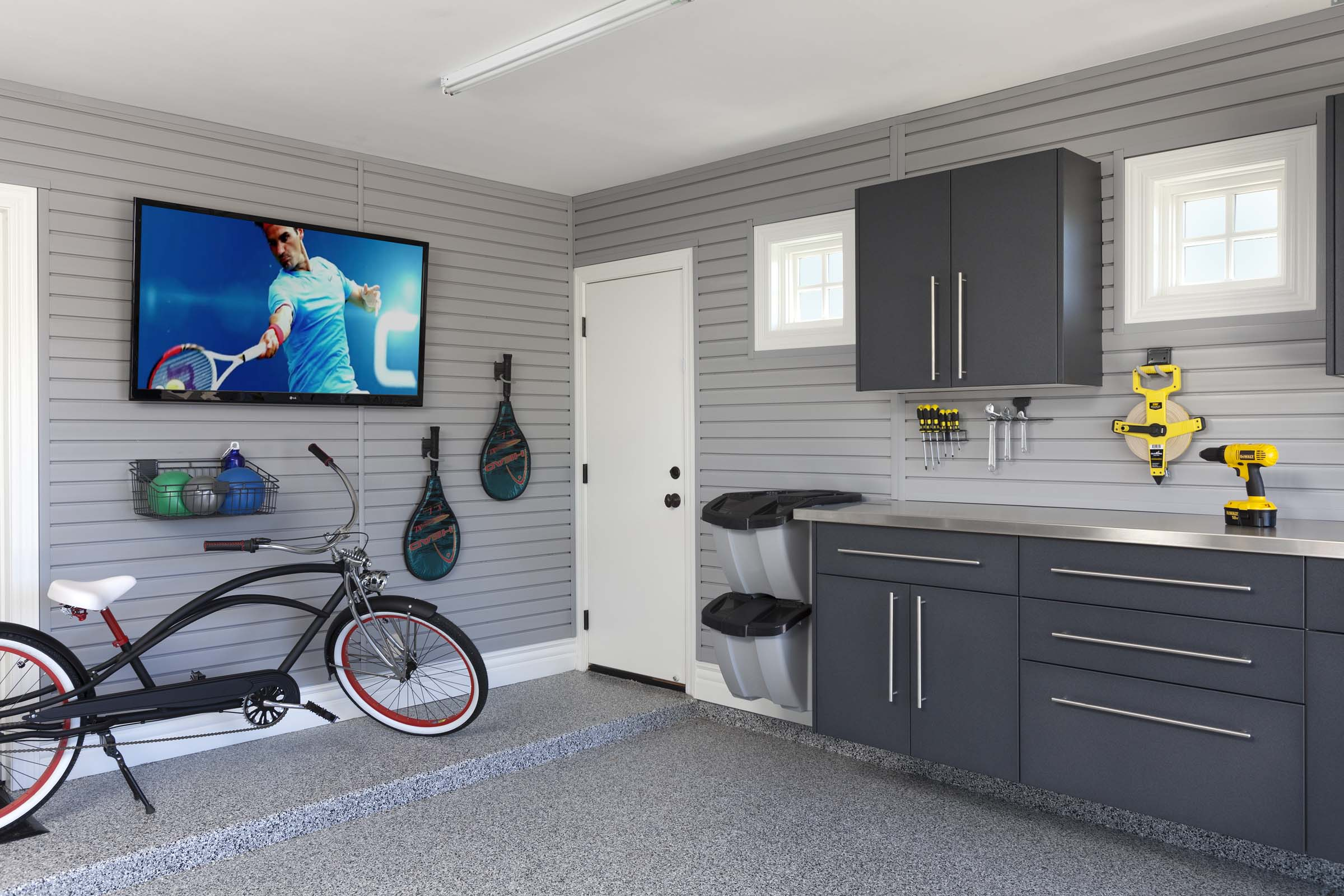 Wall mounted cabinets, upgraded drawer hardware and stainless countertops make this garage feel like another room in the house. Continuous slatwall panels maximize convenience and keep clutter at bay.  Call Closets of Tulsa  now for your FREE consultation and 3-D garage design:  918.609.0214