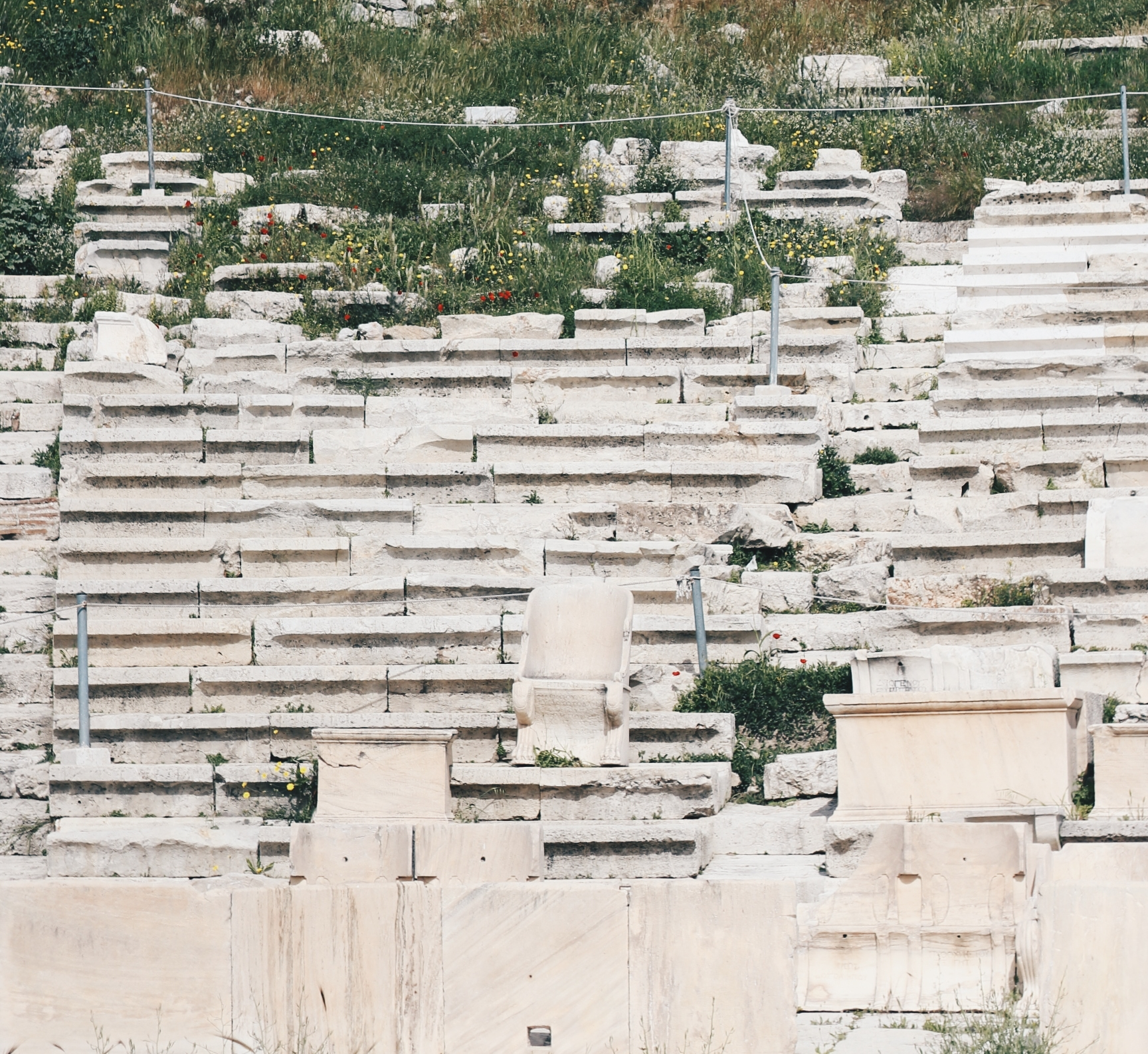 """Phang Zi Xin  """"VIP Seats At Theatre of Dionysus"""" , 22 March 2018. A picture of the VIP seats at the Theatre of Dionysus. At the center of the picture, there is a marble chair with back support, and the rows of seats towards the background there are foliage growing."""