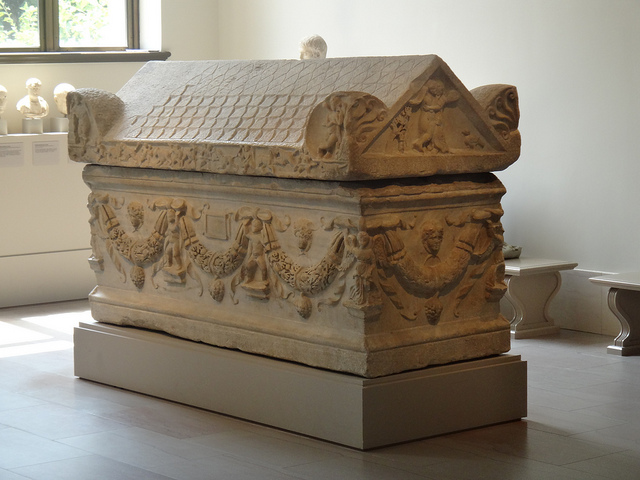 Image of an ancient greek coffin made of stone on display, decorated with carvings at the roof and sides.