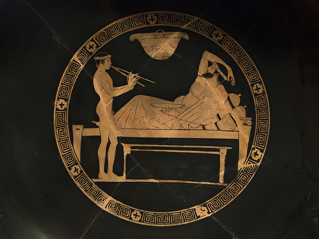Egisto Sani,  Symposiast with a male aulos- player , 6 May 2013. CC BY-NC-SA 2.0.  A naked young performer playing an aulos (Ancient Greek wind instrument) for a bearded man, who is lying on a table with a kylix on his left hand.   Fun Fact: Refer to the picture, the entertainment was often provided by the symposiasts themselves, where they would show off their skills even though the fact was that they were tipsy half the time.