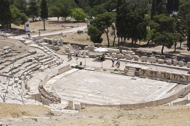 """Aleksandr Zykov,  """"Theatre of Dionysus"""" , 8 June 2010. A picture of the Theatre of Dionysus on a sunny day. In the middle ground there are ten tourists, and in the background, there are numerous trees."""